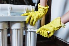 Le plombier dans les changements jaunes de gants de m?nage arrosent des filtres Cartouches filtrantes changeantes de l'eau de d?p photographie stock