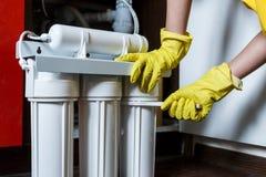 Le plombier dans les changements jaunes de gants de m?nage arrosent des filtres Cartouches filtrantes changeantes de l'eau de d?p photos stock