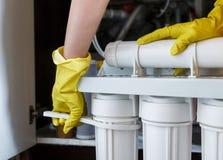 Le plombier dans les changements jaunes de gants de m?nage arrosent des filtres Cartouches filtrantes changeantes de l'eau de d?p images stock