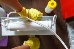 Le plombier haut ?troit dans les changements jaunes de gants de m?nage arrosent des filtres Cartouches filtrantes changeantes de  photos libres de droits