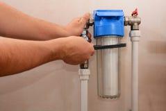 Le plombier installe une nouvelle cartouche pour le filtre d'eau Système de filtre pour le traitement de l'eau Image libre de droits