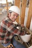 Le plombier répare la toilette Photo libre de droits