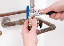 Le plombier remet fixer une valve avec la clé Photographie stock libre de droits