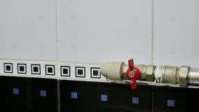 Le plombier tournent en marche et en arrêt la conduite d'eau dans la salle de bains banque de vidéos