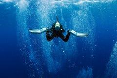 Le plongeur nage dans des bulles d'air comme dans le tourbillon images stock