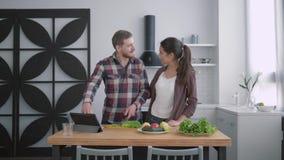 Le poids sain, épouse heureuse avec le mari prépare les aliments sains des légumes et des verts selon les la prévisions de régime banque de vidéos