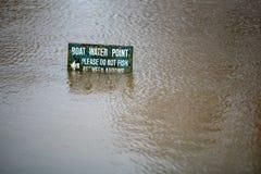 Le point d'eau ironique de bateau ne pêchent pas le signe sous des eaux d'inondation Photographie stock