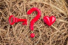 Le point d'interrogation avec la clé rouge et le coeur objectent sur la texture de foin Photos libres de droits