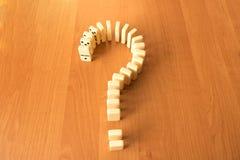 Le point d'interrogation des dominos le frotte avec le poing sur le fond en bois images stock