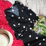 Le point de polka noir et rouge s'habille sur un fond en bois photographie stock libre de droits