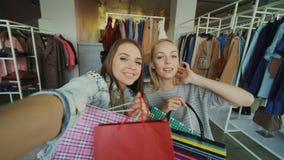 Le point de vue a tiré de deux belles jeunes femmes faisant le selfie avec des sacs en papier chez le département d'habillement d banque de vidéos