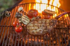 Le poisson de mer blanc de bifteck juteux a grillé et a grillé les légumes, les tomates-cerises et la courgette, plan rapproché d photographie stock libre de droits