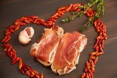 Le poivre d'un rouge ardent est rayé sous forme de coeur Une branche de thym, un clou de girofle d'ail Sandwichs faits à partir d Photographie stock libre de droits