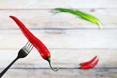Le poivre de piment d'un rouge ardent avec de l'eau se laisse tomber sur la fourchette Image libre de droits