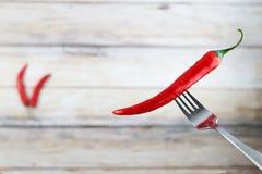 Le poivre de piment d'un rouge ardent avec de l'eau se laisse tomber sur la fourchette Photographie stock