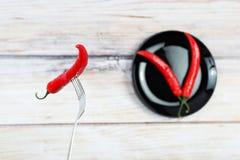 Le poivre de piment d'un rouge ardent avec de l'eau se laisse tomber sur la fourchette Images libres de droits
