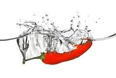Le poivron rouge a relâché dans l'eau avec l'éclaboussure image stock