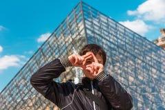 Le pojken i Paris inrama att göra en gest framme av Louvrepyraen arkivfoto