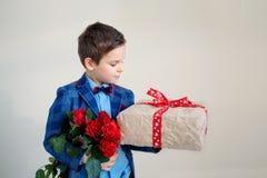 Le pojken med buketten av blommor och en gåva på en ljus bakgrund fotografering för bildbyråer