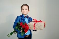Le pojken med buketten av blommor och en gåva på en ljus bakgrund arkivfoton
