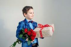 Le pojken med buketten av blommor och en gåva på en ljus bakgrund royaltyfri fotografi