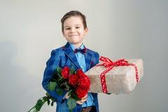 Le pojken med buketten av blommor och en gåva på en ljus bakgrund arkivfoto