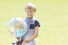Le pojken med ett jordklot utanför Utbildning tillbaka till skolabegreppet Royaltyfri Foto