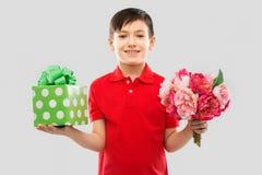 Le pojken med födelsedaggåvaasken och blommor arkivbild