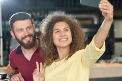 Le pojken och flickan som tar selfiesammanträde i kafét som ser smartphonen royaltyfri fotografi