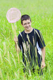 Le pojken som fångar fjärilar i ängen Arkivbild