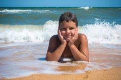 Le pojken som ligger på stranden, utomhus Royaltyfri Bild