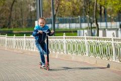Le pojken som rider en sparkcykel Arkivfoton
