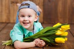 Le pojken som rymmer en bukett av gula tulpan i händer som sitter på trägolv arkivbild