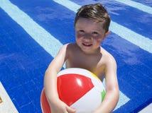 Le pojken som spelar med bollen på simbassängen Royaltyfria Bilder