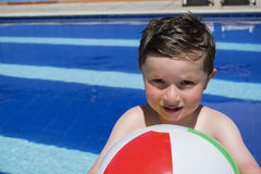 Le pojken som spelar med bollen på simbassängen Royaltyfri Foto