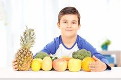 Le pojkesammanträde på tabellen mycket av frukt- och grönsakindooen Royaltyfri Fotografi