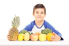 Le pojkesammanträde på tabellen mycket av frukter och grönsaker Arkivbild