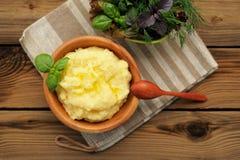 Le Polenta avec la pousse de basilic dans la cuvette en bois avec de la salade verte et courtisent Images libres de droits