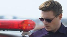Le policier déterminé acceptant l'appel et entrant dans la voiture de patrouille, préparent pour l'aide clips vidéos