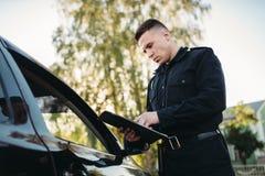 Le policier dans l'uniforme écrit très bien au conducteur femelle images stock