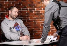 Le policier interroge le détenu Photographie stock libre de droits