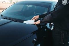 Le policier masculin dans l'uniforme écrit une amende sur la route photo libre de droits