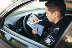 Le policier masculin s'asseyant dans la voiture et écrit une amende photos libres de droits