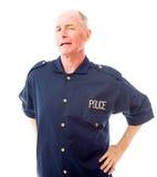Le policier se tenant avec le sien arme sur les hanches Image stock