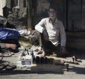 Le polisseur fier de chaussure et ses outils photos libres de droits