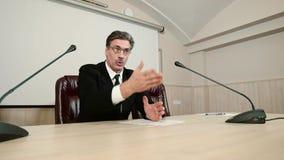 Le politicien répond sévèrement à une question à une conférence de presse, faisant des gestes à la main et parlant avec émotion é banque de vidéos