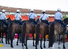 Le poliziotte sono sul loro cavallo Immagini Stock