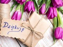 Le polonais REMERCIENT VOUS de carder et le bouquet de tulipe sur le fond en bois blanc Photographie stock