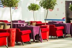 Le poltrone rosse e beige sono accanto alle tavole del ristorante, che sono coperte di tovaglie lunghe di Borgogna Fotografia Stock Libera da Diritti