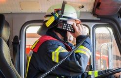 Le pompier dans un camion de pompiers drived et étincelle avec le poste radio Image stock